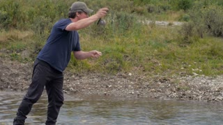 A middle age man fly fishing and his line gets snagged in a river in the mountains of Montana.