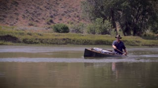 A middle age outdoorsman paddles a blue canoe down a river and smiles. There are camping supplies packed into the wooden canoe.