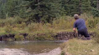 A middle aged man fly fishing in a river in Montana skillfully catches a fish