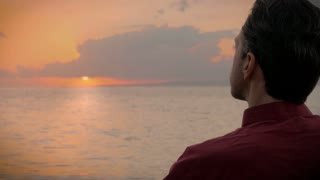 A middle aged man in a red shirt enjoys drinking a cup of coffee as he watches a beautiful and colorful sunrise over the ocean while relaxing, and thinking about the great things in store for the day.