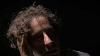 A middle aged man shows signs of withdrawal from a drug or has mental illness in dramatic lighting.