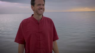 A middle aged man smiles and looks inspired by life overlooking the beach during sunrise or sunset on his early retirement. He is healthy, his family is well and everything in his life is perfect.