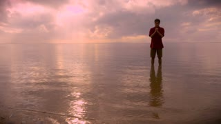 A middle aged man stands alone in the calm water of the ocean praying with hands clasped together during sunrise or sunset with reflections of the sun on the water.