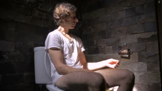 A middle aged man wearing a t-shirt in dramatic lighting sitting on a toilet grabs some toilet paper
