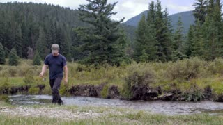 A middle aged man with a fishing rod walks past the camera away from a river in the Montana wilderness without a fish.