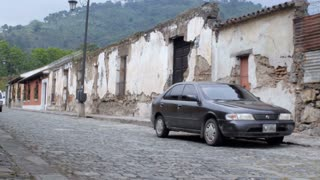 A mini bus drives down the cobble stone streets of Antigua, Guatemala past crumbling walls due to prior earthquakes in this seismically active region