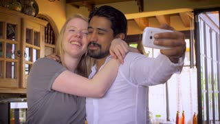 A mixed interracial young millennial couple in 20's and 30's take selfies on a cell mobile phone of each other being playful, affectionate, and silly in the morning at home in the kitchen.