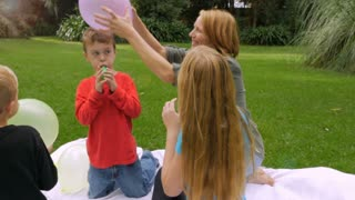 A mom rubs a balloon on her youngest redheaded son to create static electricity outside in a park - slowmo steadicam