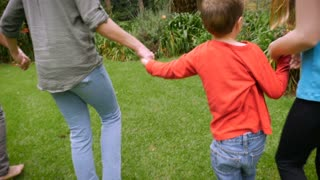 A mother and her son and daughter hold hands as they walk through the grass - slowmo. The camera follows the shortest kid - steadicam