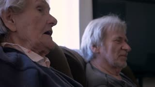 A mother and son both in their golden years talking with each other on a sofa in 4k