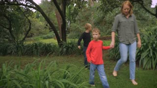 A mother brings her son to the rest of her family of 5 and walks in a park to join hands together - slowmo steadicam