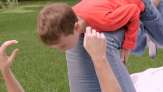 A mother plays with her young son on her legs while he hugs her and talks to her outside in a park like setting during the day - slow motion