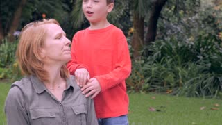 A nervous mother is concerned and distracted by something while her son massages her shoulders - slowmo