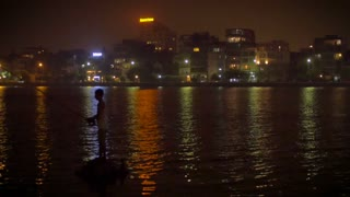 A night fisherman fishes against the city night life with the color reflections of the cityscape in the background in Hanoi, Vietnam.