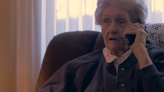 A old woman in her 90s hangs up the phone and continues talking in 4k dolly shot.