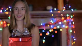 A pretty blond haired woman opens a gift with colored lights behind her