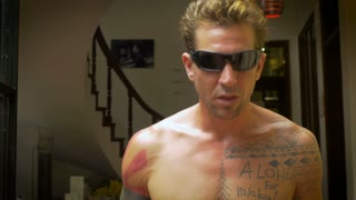 A profile of a shirtless muscular young caucasian man with tattoos in his 20s smiles while wearing sunglasses, puts a toothpick in his mouth, nods his head, and takes the toothpick out again.