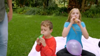 A redheaded mom comes to help her youngest son blow up balloons - slowmo steadicam