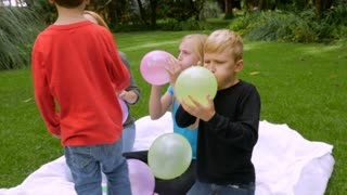 A redheaded mother and her 2 sons and daughter blow up balloons together outside all working towards a common goal - slowmo