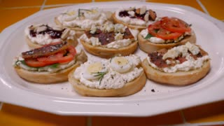 A selection of gourmet appetizers or crostinis on a plate with tomato, cheese, bacon, egg, nuts, basil, rosmary, and jam - push in
