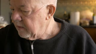 A sick elderly man removes the oxygen tubes from his nose in his home in slow motion
