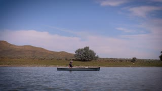 A single middle age man canoes down the Missouri river with camping gear against the backdrop of big sky country in Montana.