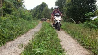 A skillful motorcycle rider driving in the mountains and jungles of Bali on a very narrow road.