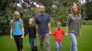 A smiling happy family of 5 look at and walk towards the camera - slowmo steadicam
