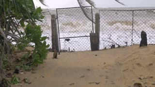 A storm surge rushes through a closed chain link fence representing rising ocean waters, unusual weather patterns, climate change, and beach erosion