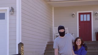 A thief wearing a ski masks stands in front of a contemporary, modern, house with his arm around a woman