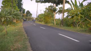 A two lane paved road with a couple of motorcycles and a car drive by in Bali, Indonesia