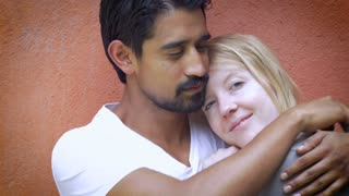 A very attractive mixed racial couple in love embrace, smile, and kiss against an orange wall showing affection and love for one another.
