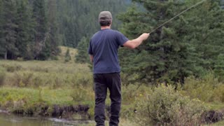 A very skilled fly fisherman approaches a bend in a river and casts his line and crouches down