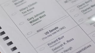 A voter fills in Wall Street in the write-in box for president on their ballot