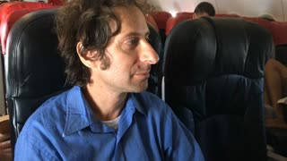 A weary traveler tries to buy something with cash on an airplane
