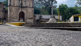 A wide shot of an old church and empty plaza in Antigua, Guatemala in the day. A bird lands gracefully on top of the church entrance.