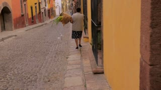 A woman walks down the empty cobblestone streets of San Miguel de Allende with flowers without an automobile traffic in slow motion steadicam shot.