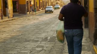 A women with a broom passes a pedestrian on the sidewalk on the cobblestone street in Mexico