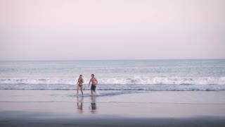 A young athletic woman in a bikini and six pack abs runs out of the ocean with her boyfriend or husband. The two runners are having a great time together as a couple.