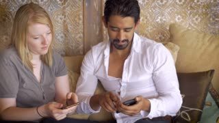 A young attractive couple each surf on their cell phones mobile devices and share with each other, lovingly, what they've been looking at. Dolly shot against a modern home and comfortable sofa.