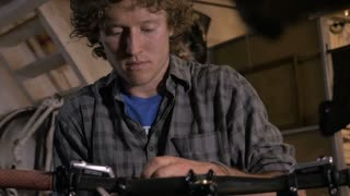 A young bike mechanic works at the front end of a bicycle with a wrench - dolly shot
