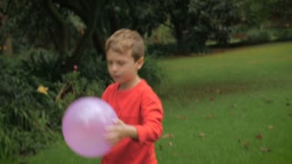 A young boy brings a balloon to his mother outside - slow mo
