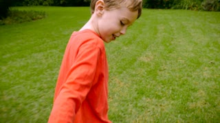 A young boy leading and pulling someone while running through the grass - slowmo. It appears that he is pulling his mom or dad towards something he is excited about.