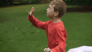 A young boy plays with his mother hitting a balloon outside in a park back and forth - slowmo
