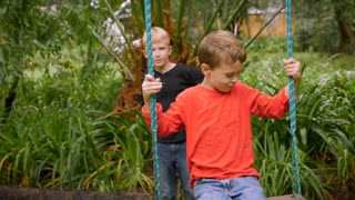 A young boy tries to get going on a swing by himself with another boy standing behind him - slowmo
