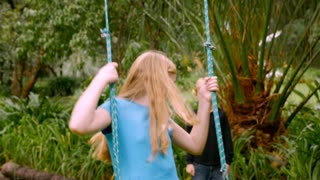 A young girl with blond hair on a swing kicks her legs back and forth while a boy pushes her - slowmo
