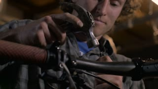 A young handsome man carefully uses a hammer to hit a metal object into a cable for a bicycle repair