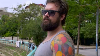 A young hipster man with a full beard and colorful full back tattoos turns his back to the camera, drinks a beer, and walks away as the camera follows him outside along a lake in the summer.