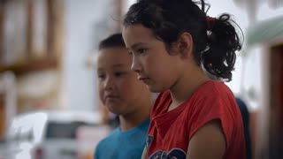 A young latin girl and boy talking and shrugging her shoulders - slowmo