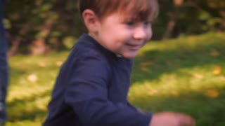 A young little toddler boy in a blue shirt running past the camera and picks up a leaf from the ground in a park or the backyard of a house in slow motion.